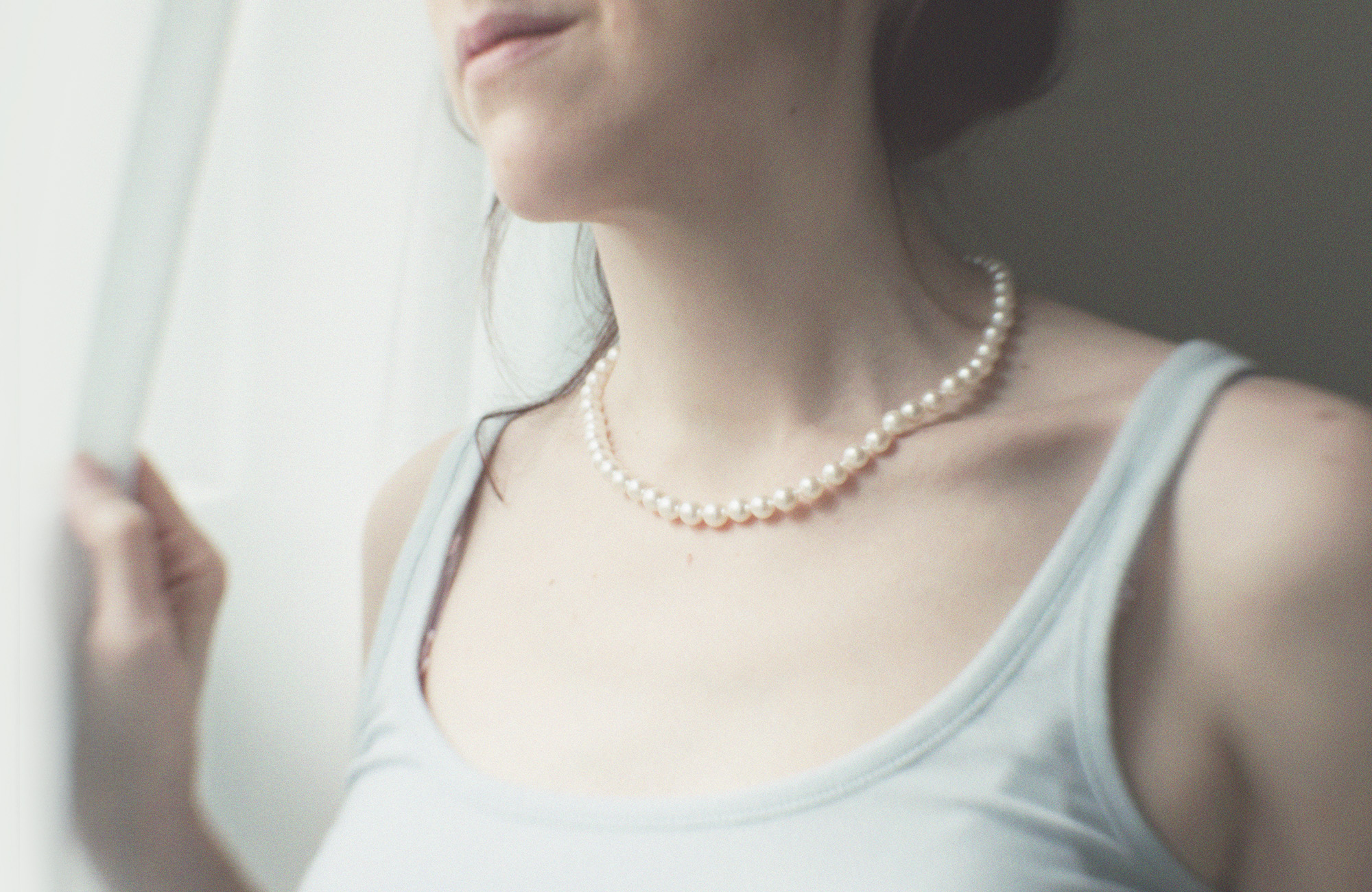 Woman in pearl necklace looking out of the window